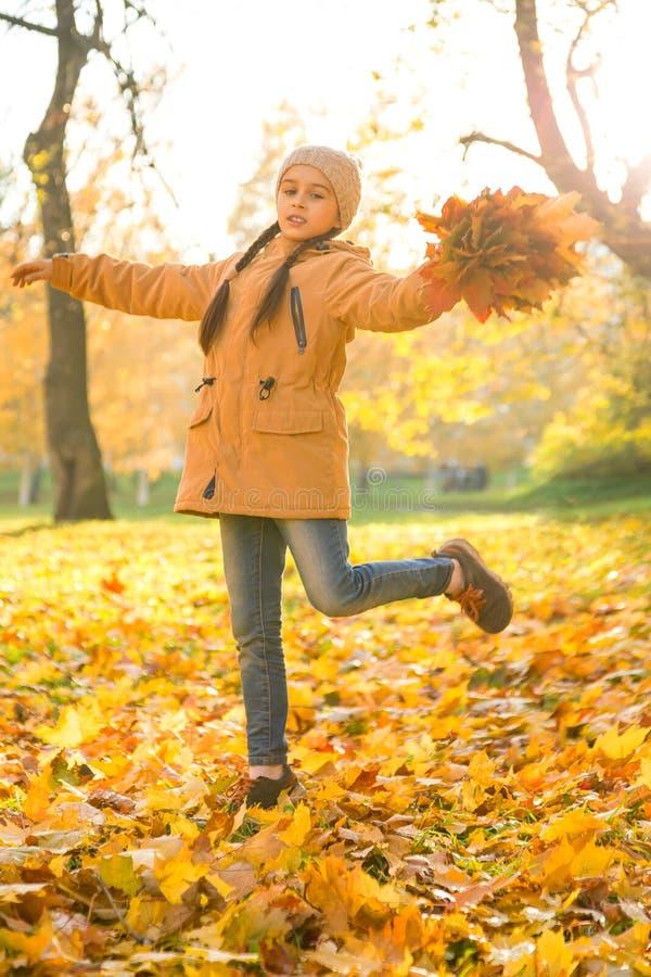 Szczęśliwy mała dziewczynka taniec na spadać liściach klonowych w jesień parku na rozochoconym spadku dniu, vertica fotografia royalty free
