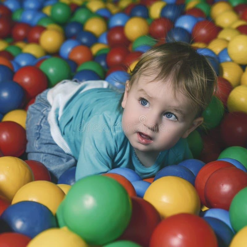 Szczęśliwy małe dziecko bawić się na boisku wypełniającym z kolorowym pl fotografia stock