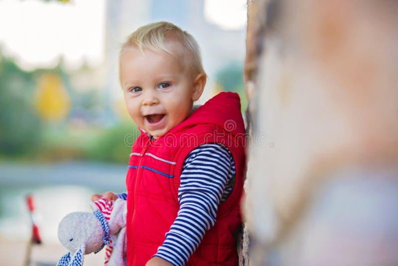 Szczęśliwy małe dziecko, chłopiec śmia się i bawić się z koić, obrazy royalty free