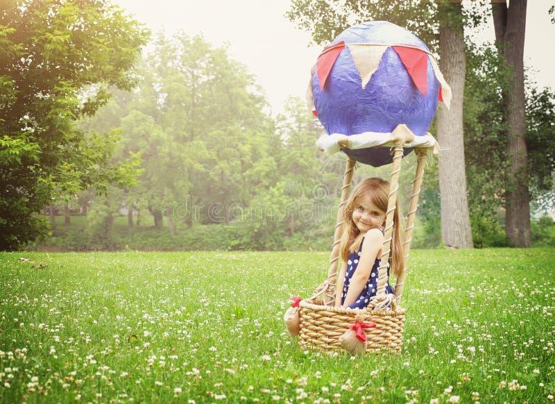 Szczęśliwy małego dziecka obsiadanie w gorące powietrze balonie obrazy stock