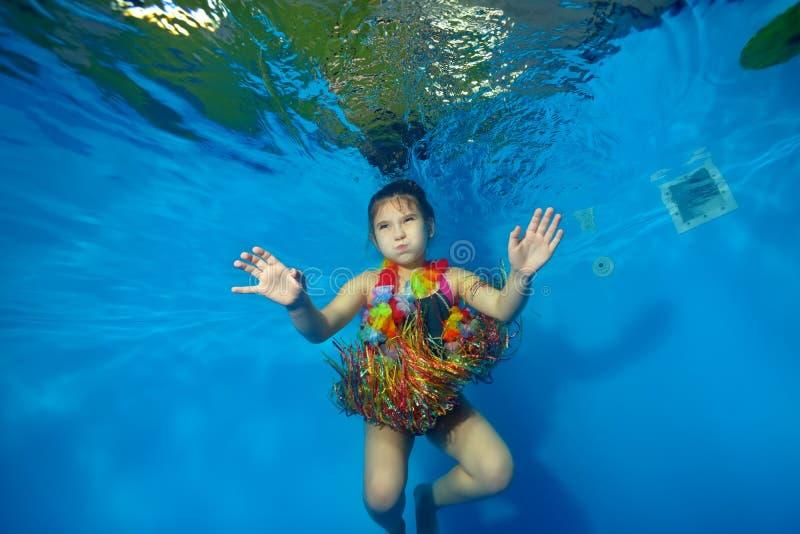 Szczęśliwy małej dziewczynki dopłynięcie, taniec podwodni w basenie w kostiumu dla karnawału na błękitnym tle i fotografia stock