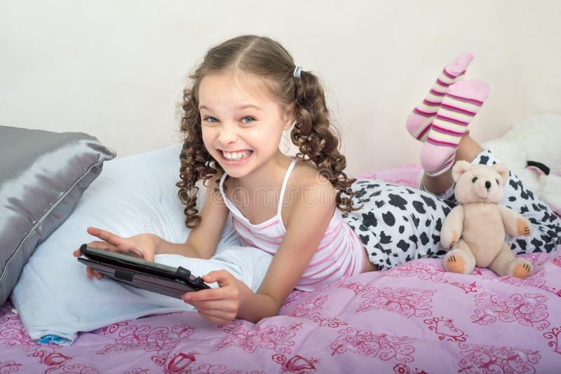 Szczęśliwy małej dziewczynki lying on the beach na łóżku z pastylka komputerem zdjęcia stock