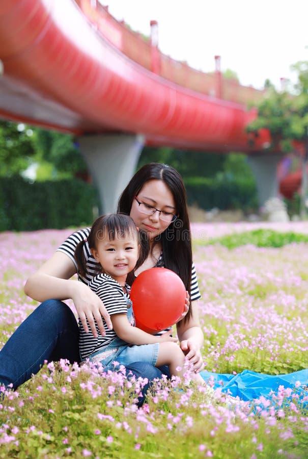 Szczęśliwy mały śliczny dziewczynka uśmiech, sztuka i szybko się zwiększać z matką, mama mówimy opowieść jego córka w lato parka  zdjęcie royalty free