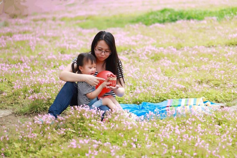 Szczęśliwy mały śliczny dziewczynka uśmiech, sztuka i szybko się zwiększać z matką, mama mówimy opowieść jego córka w lato parka  zdjęcia royalty free