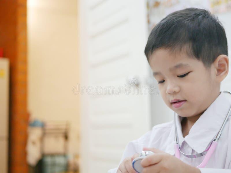 Szczęśliwy mały Azjatycki dziecko dostaje ubierający jako lekarka zdjęcie stock