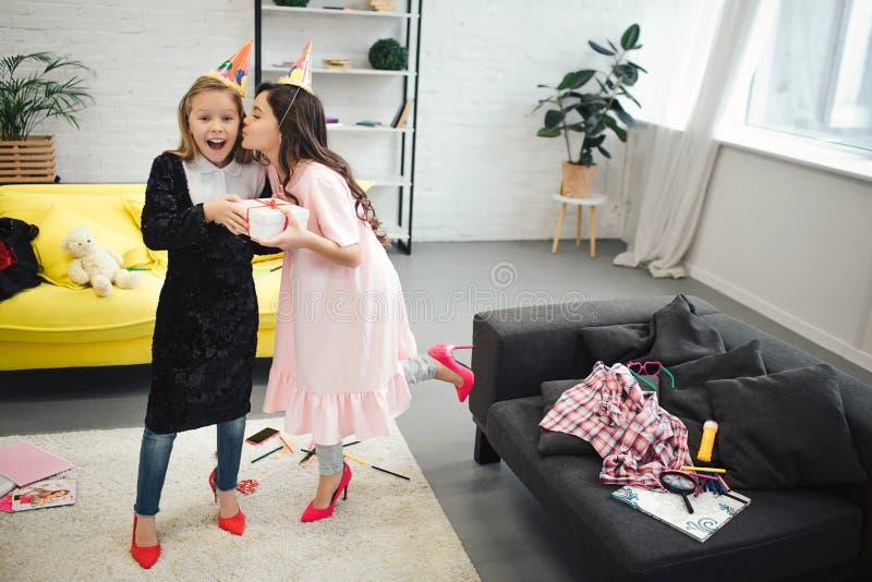 Szczęśliwy mały blondynki dziewczyny chwyt teraźniejszy od jej przyjaciela Brunetka całuje ona w policzku Nastolatek odzież odzie zdjęcie stock