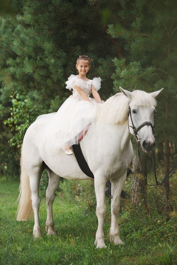 Szczęśliwy mały princess na białym koniu w lesie zdjęcie stock