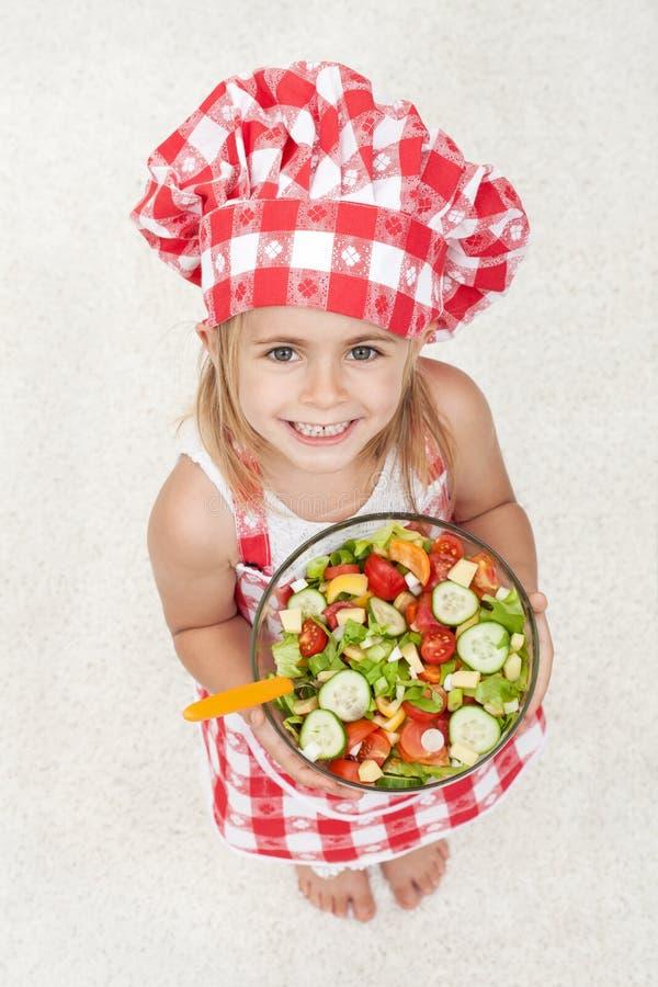 Szczęśliwy mały szef kuchni trzyma puchar warzywo sałatka - patrzeć u zdjęcia royalty free