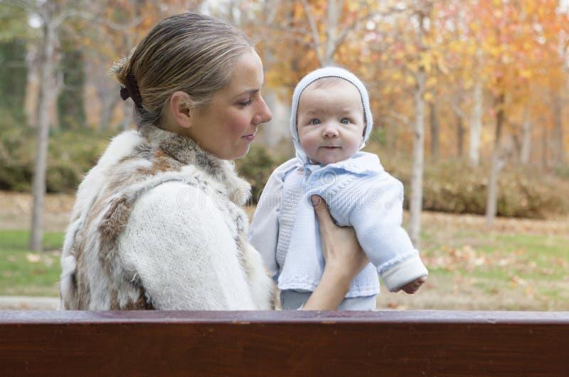 Szczęśliwy macierzysty bawić się z jego dzieckiem w parku na ławce na w zdjęcia stock
