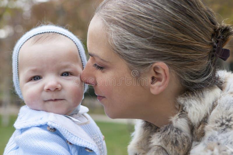 Szczęśliwy macierzysty bawić się z jego dzieckiem w parku na ławce na w fotografia royalty free
