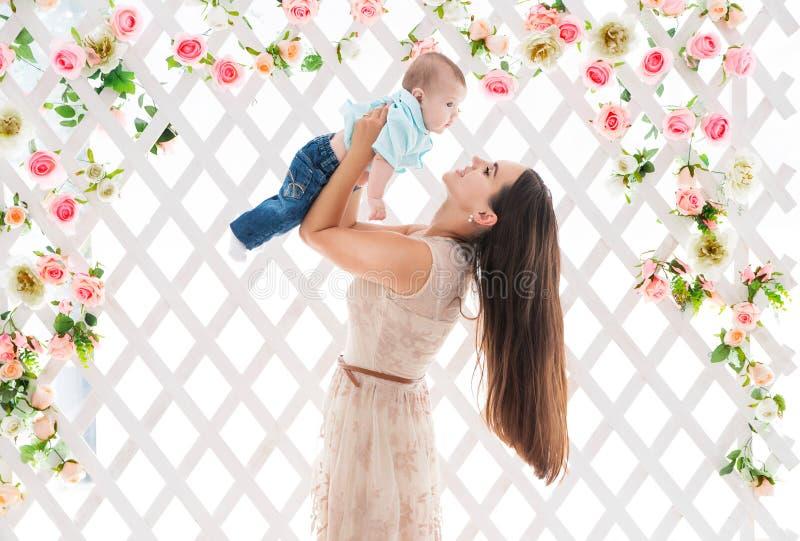Szczęśliwy macierzysty bawić się z jej synem na tle sceneria z kwiatami fotografia stock
