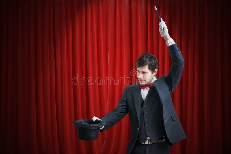 Szczęśliwy magik lub iluzjonista pokazujemy magiczną sztuczkę z jego różdżką Czerwone zasłony w tle fotografia stock