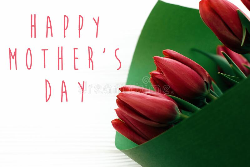 Szczęśliwy matka dnia tekst i piękni czerwoni tulipany na białym drewnianym tle Szcz??liwa macierzystego dnia kartka z pozdrowien zdjęcie stock
