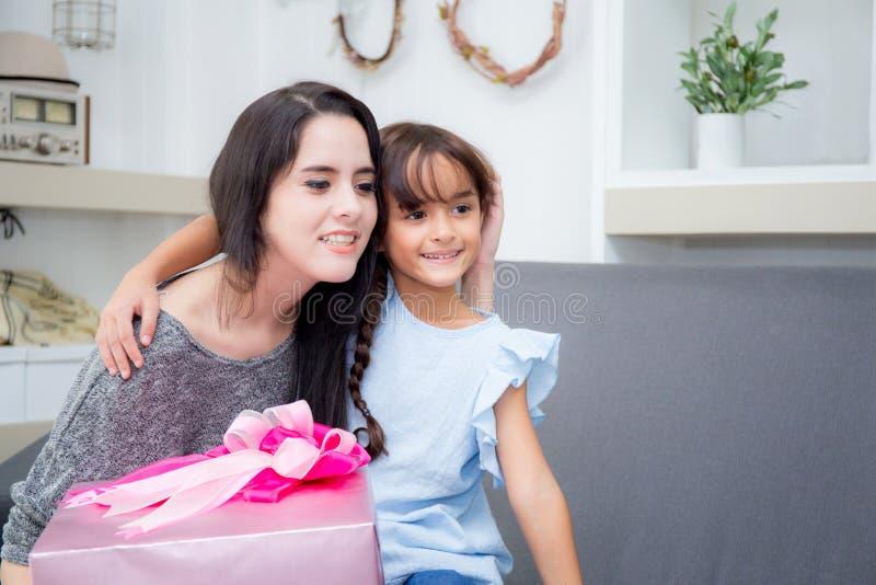 szczęśliwy matki, córki azjata z prezentem z różową całowanie matką i zdjęcie stock