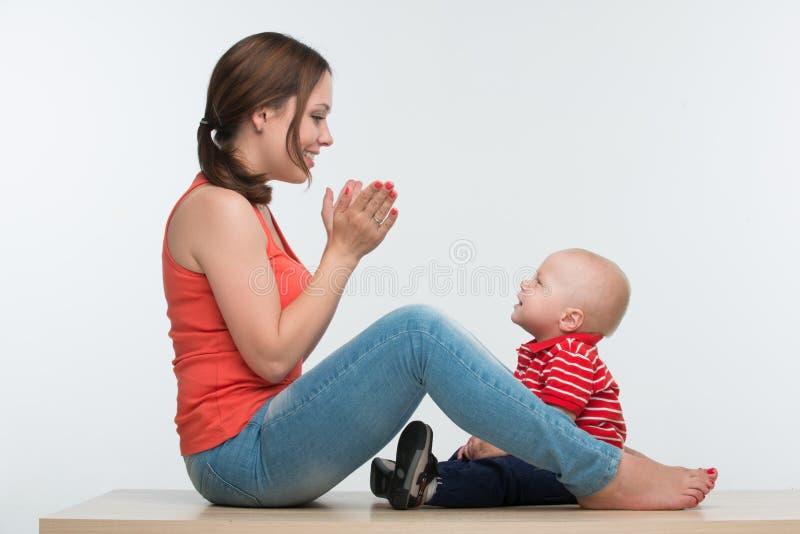 Szczęśliwy matki i berbecia syna siedzieć twarz w twarz obrazy stock