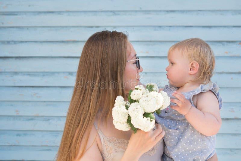 Szczęśliwy matki i córki berbeć obwąchuje małego bukiet biali kwiaty przeciw błękitnej wyklepanej ścianie Scena miłość, zdjęcia royalty free