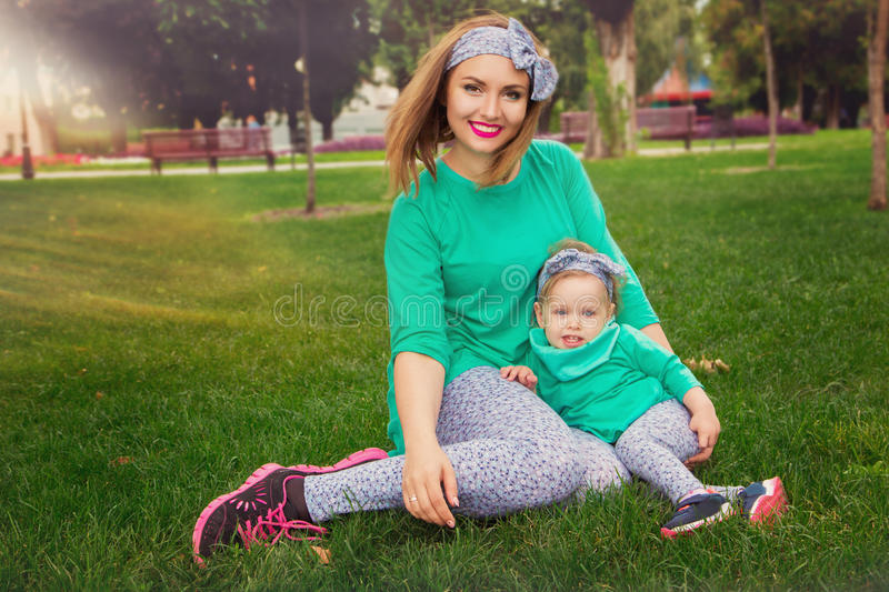 Szczęśliwy matki i córki obsiadanie na trawie fotografia royalty free