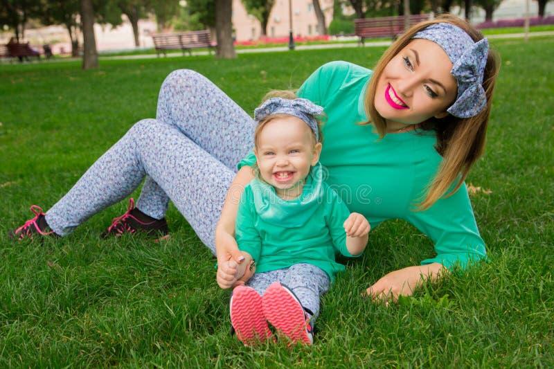 Szczęśliwy matki i córki obsiadanie na trawie obrazy stock