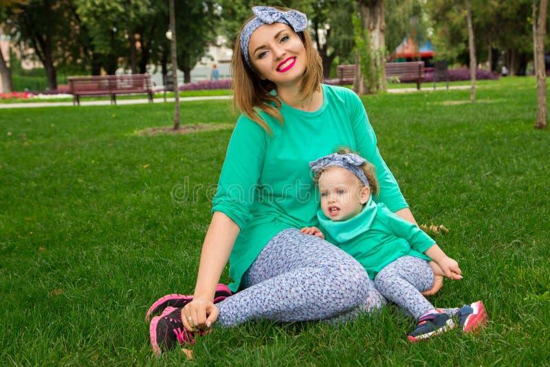Szczęśliwy matki i córki obsiadanie na trawie zdjęcia royalty free