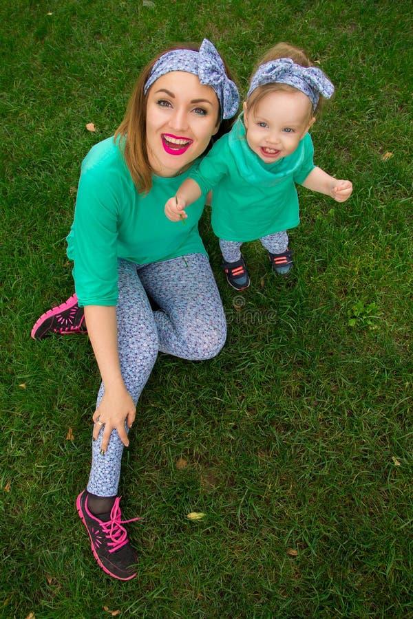 Szczęśliwy matki i córki obsiadanie na trawie obraz royalty free