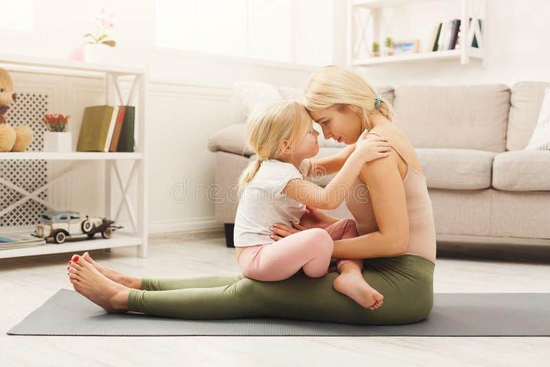 Szczęśliwy matki i córki przytulenie podczas gdy domowa joga klasa fotografia stock
