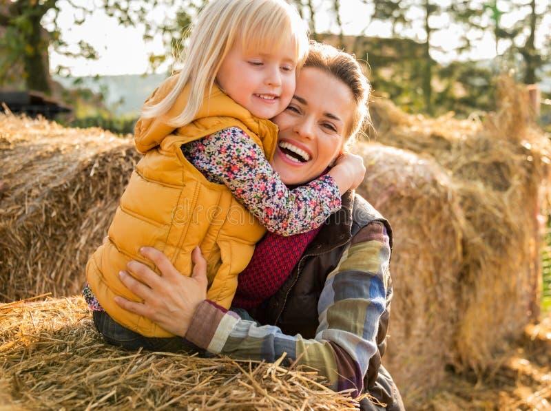 Szczęśliwy matki i dziecka przytulenie podczas gdy na haystack obraz stock