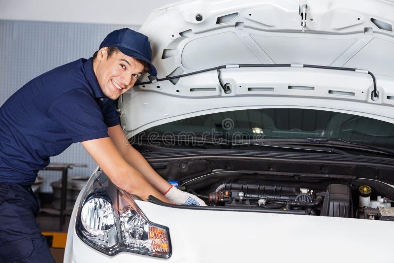 Szczęśliwy mechanik Egzamininuje Samochodowego silnika obrazy royalty free