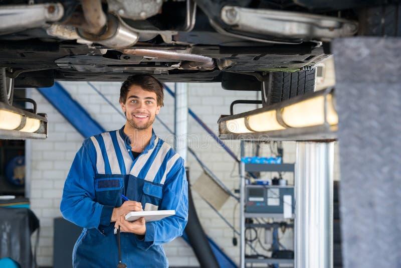 Szczęśliwy mechanika Writing Na schowku Pod samochodem zdjęcia royalty free