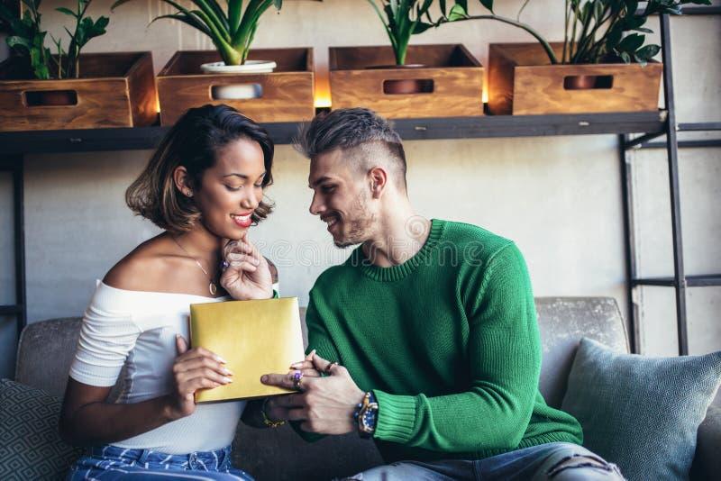 Szczęśliwy międzyrasowy pary obsiadanie w kawiarnia barze fotografia stock