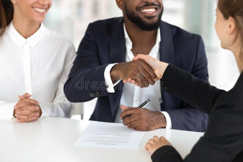 Szczęśliwy mieszany pochodzenie etniczne pary handshaking maklera znaka hipoteki kontrakt obraz royalty free