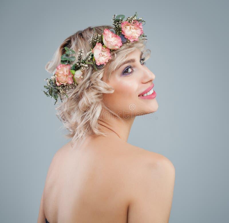 Szczęśliwy model w kwiatach, portret Piękna kobieta z krótkiej blondynki kędzierzawym włosy i makeup na błękitnym tle zdjęcia stock