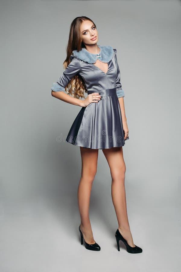 Szczęśliwy model w modnym siwieje suknię z futerkowym kołnierzem i rękawami zdjęcia stock