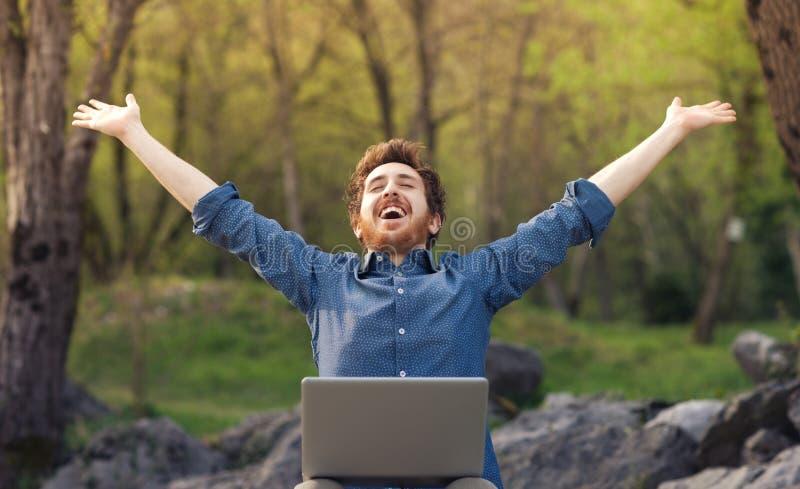 Szczęśliwy modniś z laptopem w lesie obrazy stock