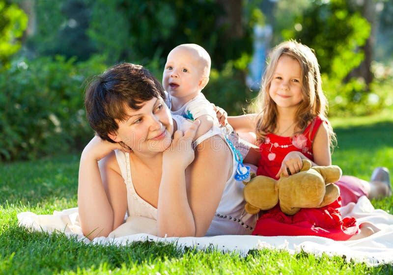 Szczęśliwy mum i jej dzieci bawić się w parku wpólnie Plenerowy pora zdjęcie royalty free