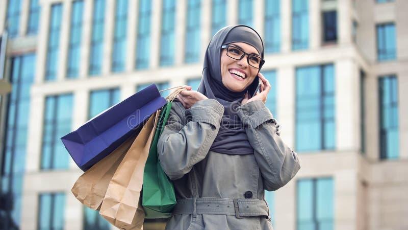Szczęśliwy Muzułmański damy gawędzenie na telefonu centrum handlowym outdoors, czarna Piątek sprzedaż fotografia royalty free