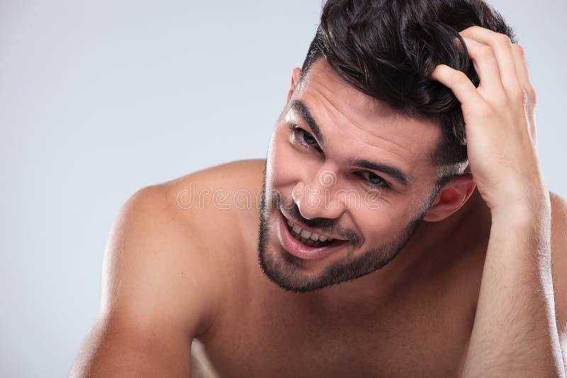Szczęśliwy nagi mężczyzna drapa jego uśmiechy i głowę obraz royalty free