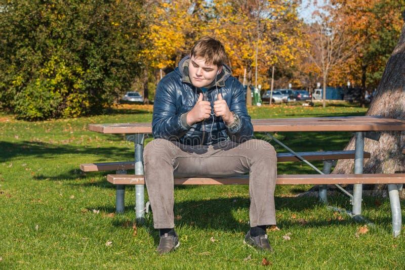 Szczęśliwy nastoletni chłopak jest ubranym hełmofony i słuchającą muzykę w jesień parku zdjęcia stock