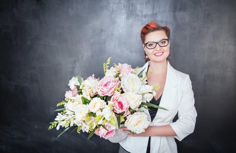 Szczęśliwy nauczyciel z kwiatami na chalkboard tle obraz royalty free
