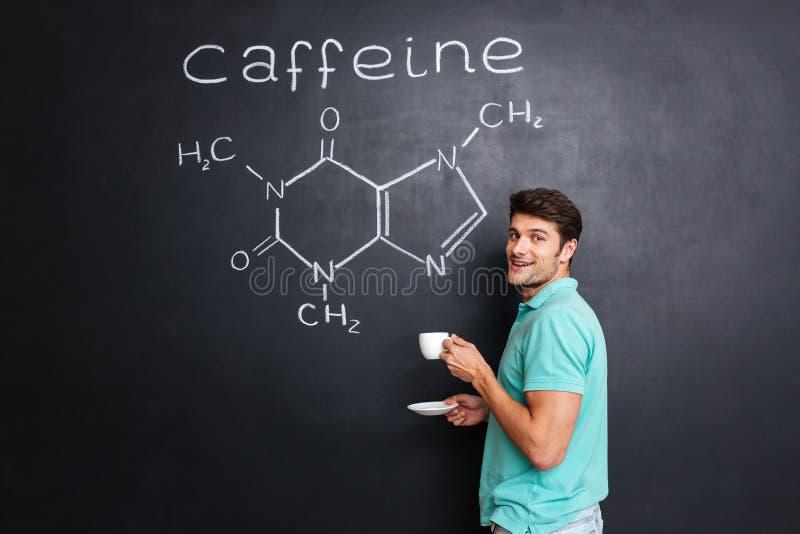 Szczęśliwy naukowiec pije kawę nad chemiczną strukturą kofeiny molekuła obrazy stock