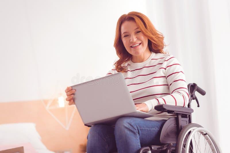 Szczęśliwy niepełnosprawny żeński freelancer pracuje w domu fotografia royalty free