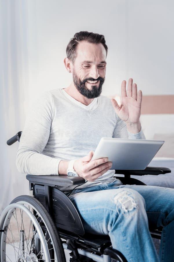 Szczęśliwy niepełnosprawny mężczyzna opowiada z przyjaciółmi obrazy royalty free