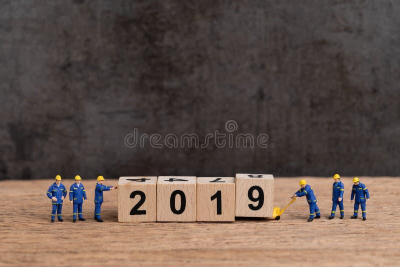 Szczęśliwy nowego roku 2019 pojęcie, śliczni miniaturowi ludzie munduruje worke obrazy royalty free