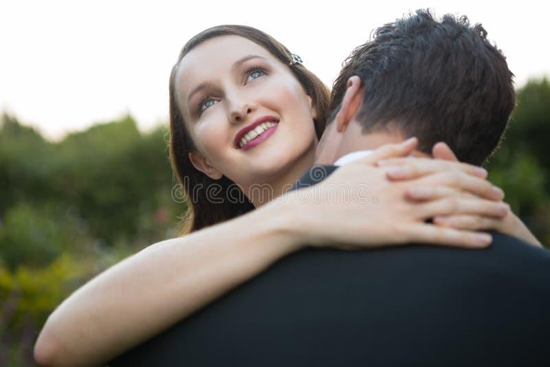 Szczęśliwy nowożeńcy pary obejmowanie podczas gdy stojący w parku fotografia stock