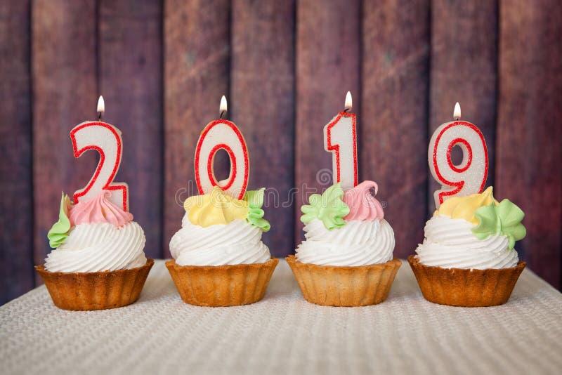 Szczęśliwy nowy rok 2019, numerowe świeczki na babeczkach z drewnianym tłem fotografia stock