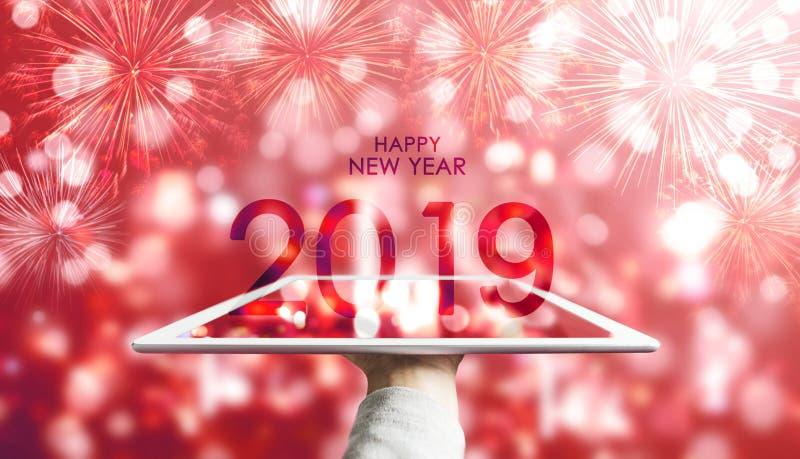 Szczęśliwy nowy rok 2019, ręka trzyma cyfrową pastylkę z czerwonym Bokeh fajerwerków tłem ilustracji