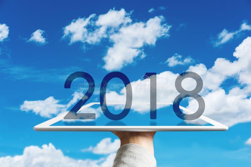 Szczęśliwy nowy rok 2018, ręka trzyma cyfrową pastylkę z zwiększającym rzeczywistości niebieskim niebem, bielem i chmurnieje obraz royalty free