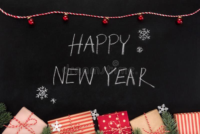 SZCZĘŚLIWY nowy rok ręki writing tekst na blackboard zdjęcie stock
