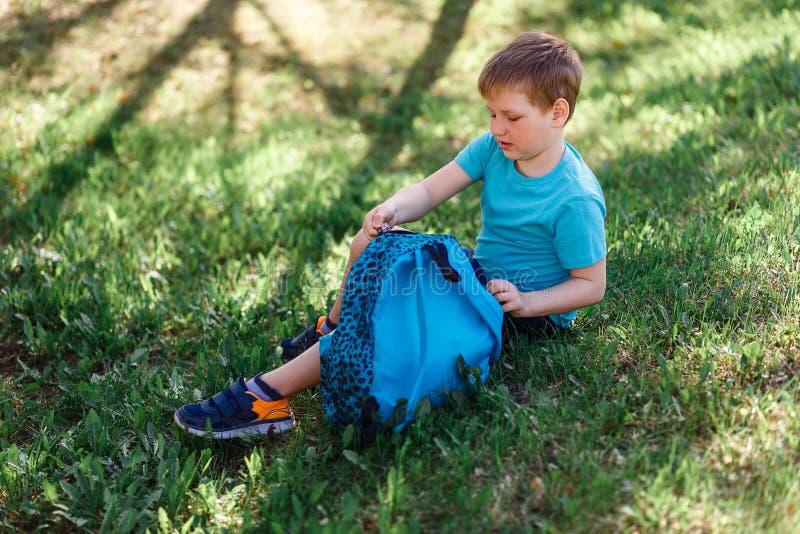 Szczęśliwy ośmioletni uczeń siedzi na zielonej trawie i otwierał jego plecaka obraz stock