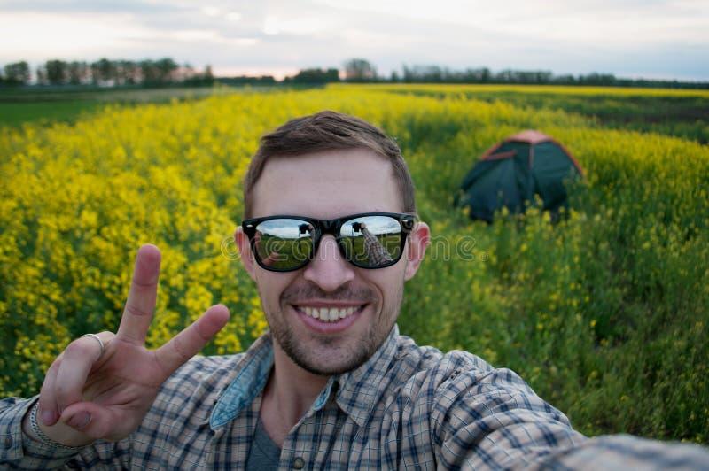 Szczęśliwy obozowicz w okularach przeciwsłonecznych robi selfie w campingu, obraz stock