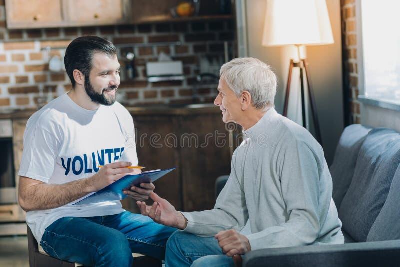 Szczęśliwy ochotniczy opowiadać z starym człowiekiem zdjęcia royalty free